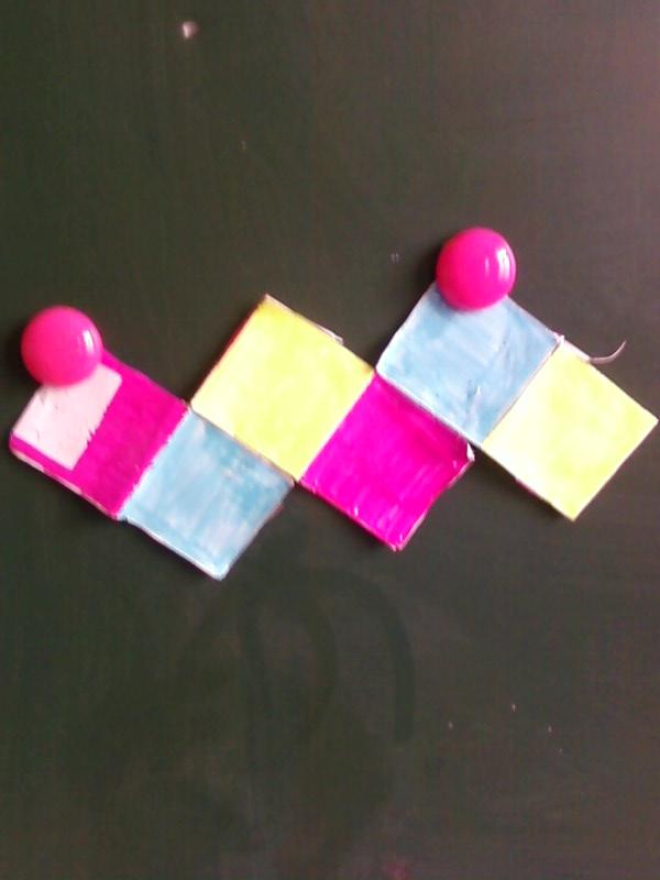 """作者: 任姝凝 (相对的面涂上相同的颜色,学生观察在""""体""""中相对的面,到展开图上的位置是什么样子。任姝凝的正方体不方便涂色,利用""""灰太郎和喜羊羊""""的图片,六个面用灰太郎、喜羊羊和懒羊羊作标记,让同学们眼前一亮)"""
